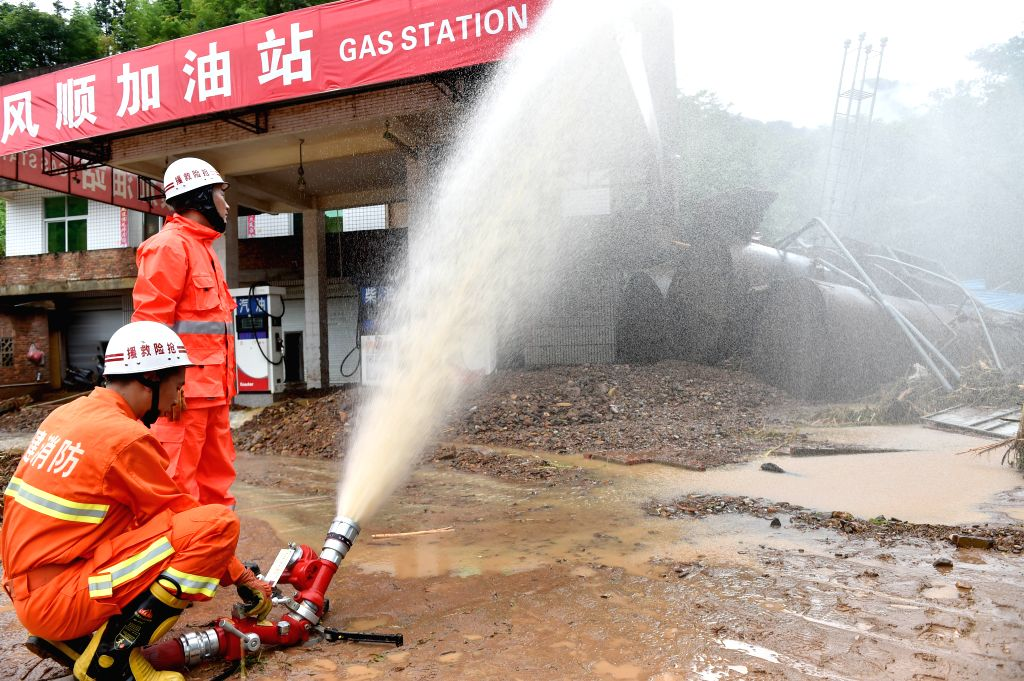 ZHANGPING, July 10, 2016 - Firemen carry out rescue work at a gas station destroyed by landslide in Zhangping, southeast China's Fujian Province, July 10, 2016. Two people have died and 17 remain ...
