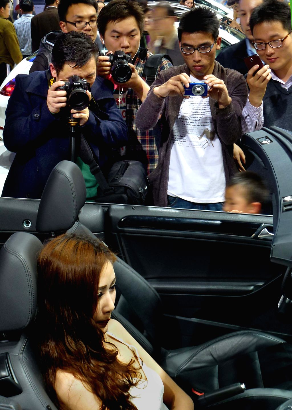 A model poses with a car at the 2014 Dahe Spring Auto Show in Zhengzhou, capital of central China's Henan Province, April 12, 2014. Over 50,000 people visited ...