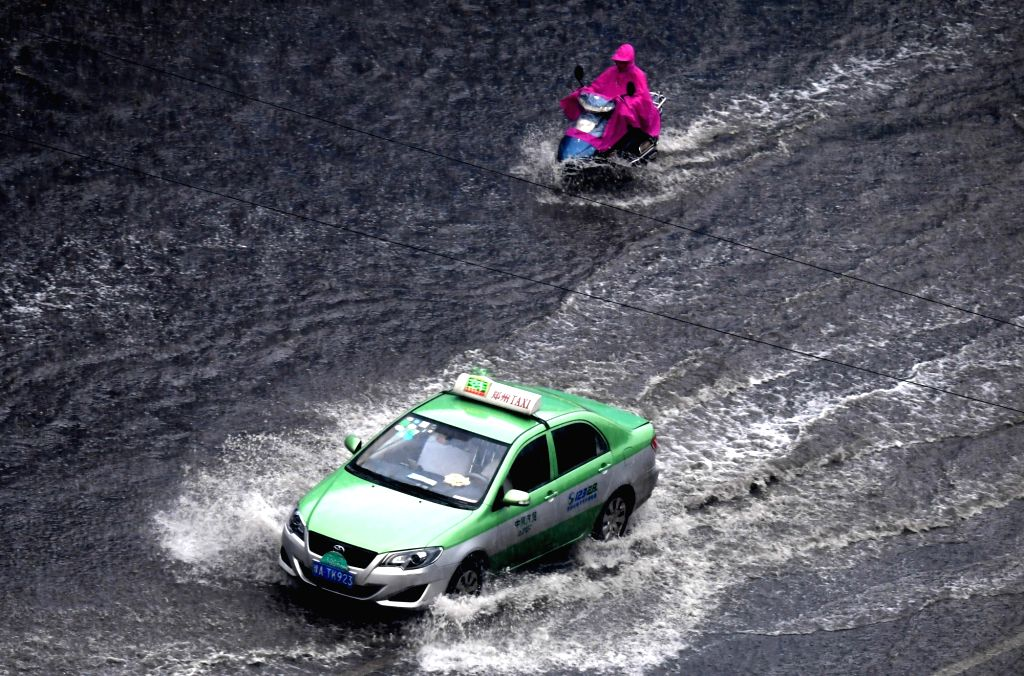 ZHENGZHOU, Aug. 12, 2017 - A car and an electric bicycle wade through a water-logged road in Zhengzhou, central China's Henan Province, Aug. 12, 2017. Heavy rain hit Zhengzhou on Saturday and caused ...