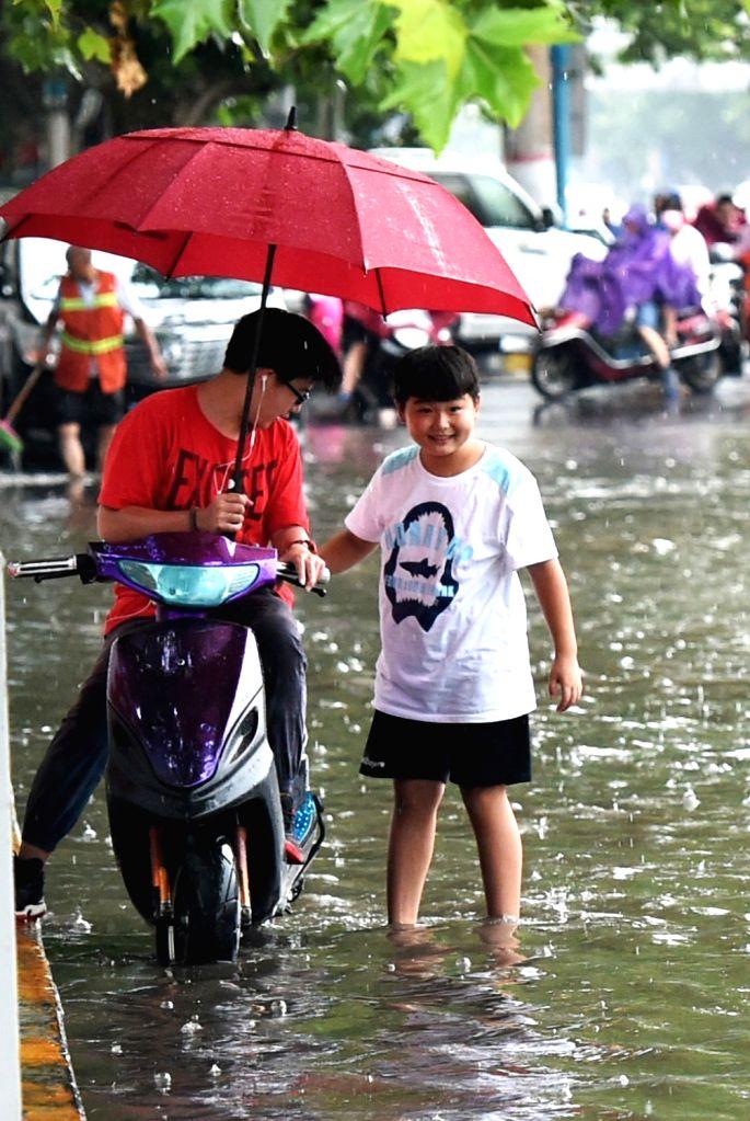 ZHENGZHOU, Aug. 12, 2017 - Residents wade through a water-logged road in Zhengzhou, central China's Henan Province, Aug. 12, 2017. Heavy rain hit Zhengzhou on Saturday and caused waterlogging.