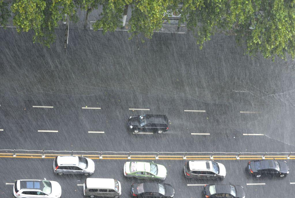 ZHENGZHOU, Aug. 5, 2016 - Cars run in rain on a road in Zhengzhou, central China's Henan Province, Aug. 5, 2016. A heavy rain hit Zhengzhou Friday. (Xinhua/Feng Dapeng)