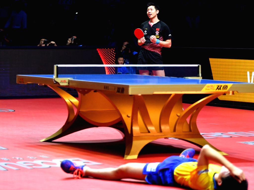 ZHENGZHOU, Dec. 13, 2019 - Xu Xin (up) of China celebrates his victory after the men's singles quarterfinal against Harimoto Tomokazu of Japan at the 2019 ITTF World Tour Grand Finals in Zhengzhou, ...