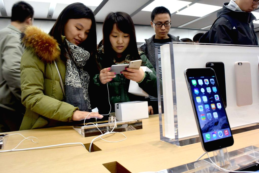 Customers try the Apple products at a newly opened Apple Store in Zhengzhou, capital of central China's Henan Province, Jan. 10, 2015. Apple inaugurated its 13th .