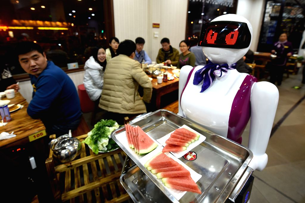 A robot waiter serves fruit to customers at a restaurant in Xuchang, central China's Henan Province, Jan. 11, 2015. The robot, worth some 13,000 dollars (80 ...