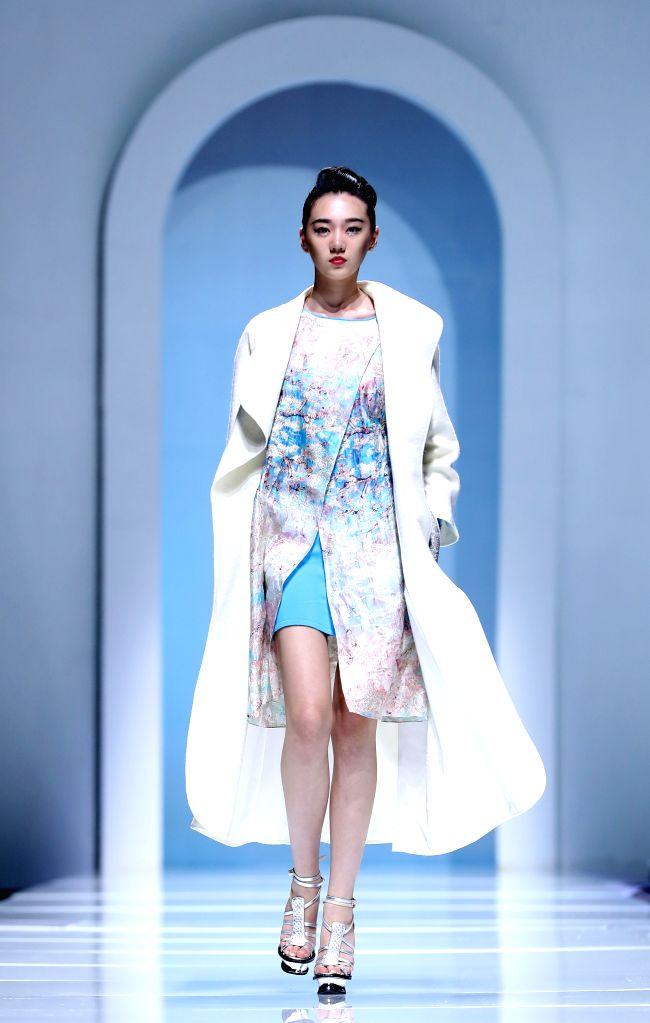 ZHENGZHOU, June 25, 2016 - A model presents a creation designed by Qi Gang during Zhongyuan International Fashion Week in Zhengzhou, capital of central China's Henan Province, June 24, 2016.