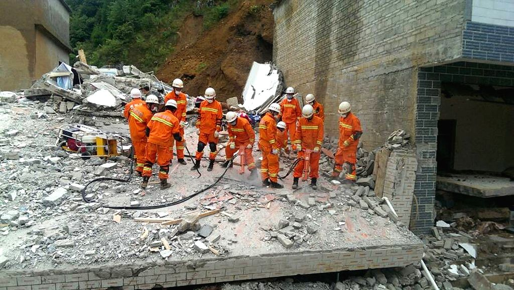 Rescuers work at the site of landslide in Dakuo Village of Zhijin County in the city of Bijie, southwest China's Guizhou Province, July 17, 2014. Six people died and