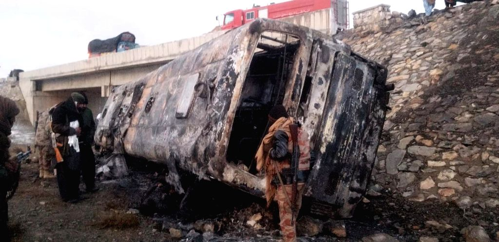 ZHOB, Dec. 13, 2019 - Photo taken with a mobile phone shows officials inspecting a burnt passenger bus at the accident site in Zhob, Pakistan's southwest province of Balochistan, Dec. 13, 2019. At ...