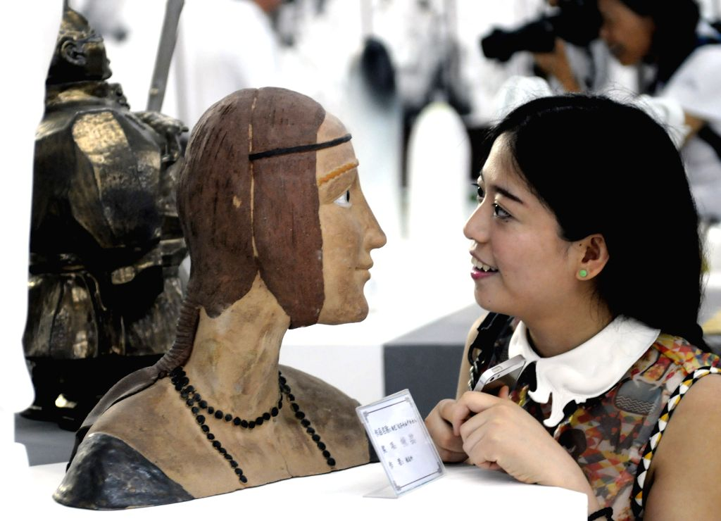 A visitor looks at a product displayed during the 14th China (Zibo) International Ceramics Expo in Zibo, east China's Shandong Province, Sept. 6, 2014. The four-day ...
