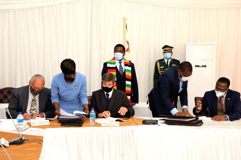Zimbabwean President Emmerson Mnangagwa (L, rear) witnesses a signing ceremony of compensation agreement at the State House in Harare, Zimbabwe, on July 29, 2020. ...
