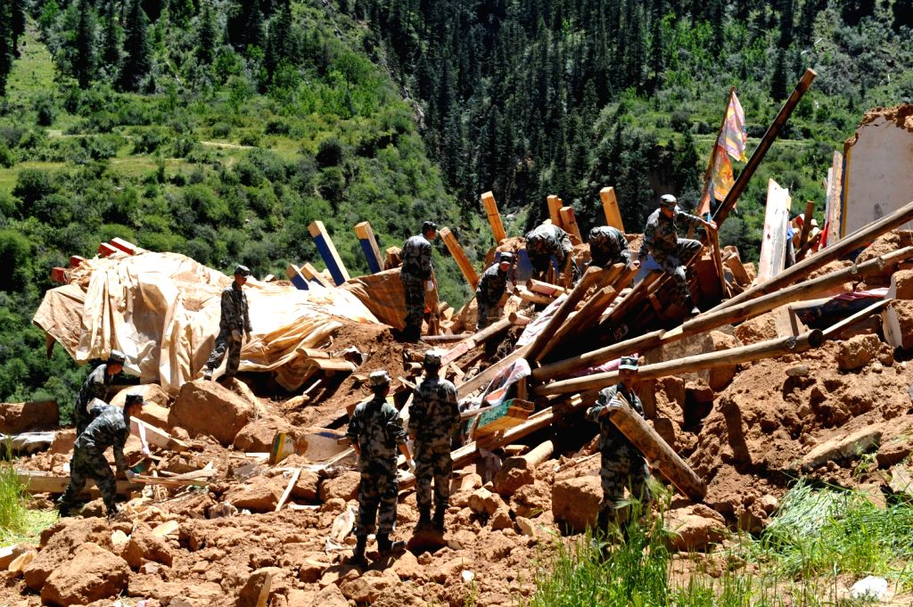 Soldiers clean a collapsed house damaged by an earthquake Zogang County in Qamdo Prefecture, southwest China's Tibet Autonomous Region, Aug. 13, 2013. No ..