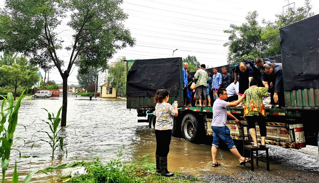 ZOUPING, Aug. 13, 2019 - Photo taken with a mobile phone shows villagers getting on a truck to move to a relocation site in Fangjiaqiao Village of Zouping, east China's Shandong Province, Aug. 12, ...