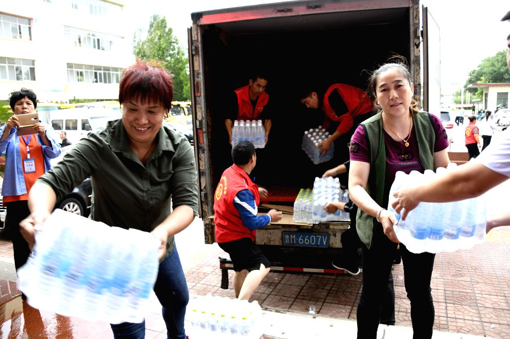 ZOUPING, Aug. 13, 2019 - Volunteers carry bottled water at Gaoxin Primary School, which now serves as a relocation site in Zouping, east China's Shandong Province, Aug. 12, 2019. More than 30,000 ...