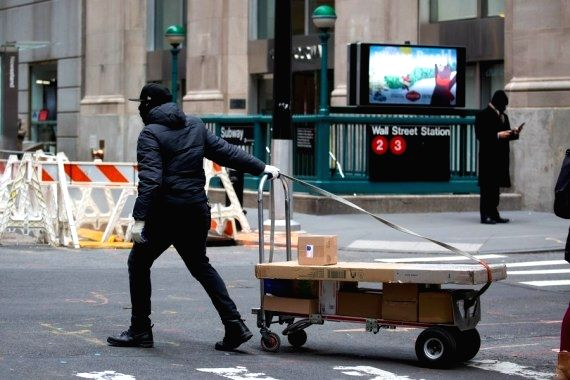A delivery worker rolls packages across Wall Street in New York, United States, Jan. 8, 2021.  (Photo by Michael Nagle/Xinhua/ians)