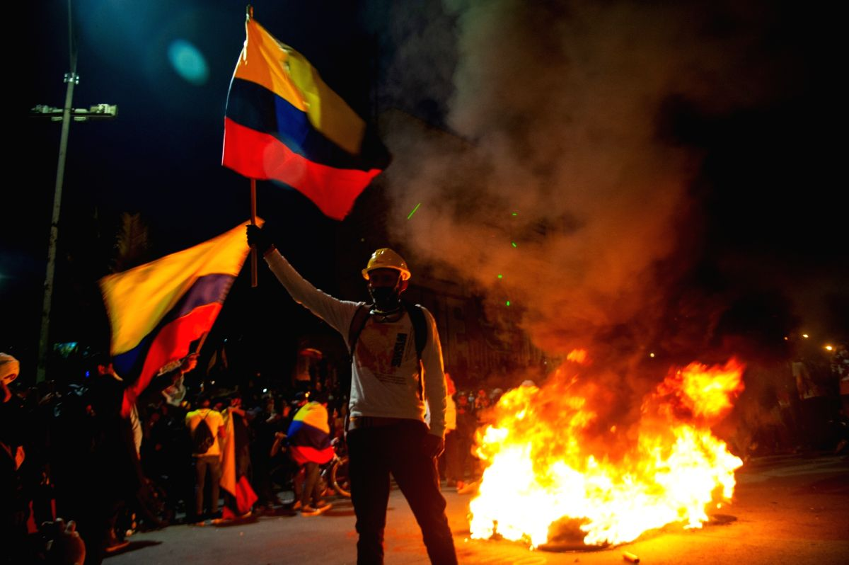 A demonstrator waves a Colombian flag in front of burnt tires during a protest against the government of Colombian President Ivan Duque Marquez(Photo: Chepa Beltran/LongVisual via ZUMA Wire/dpa/IANS)