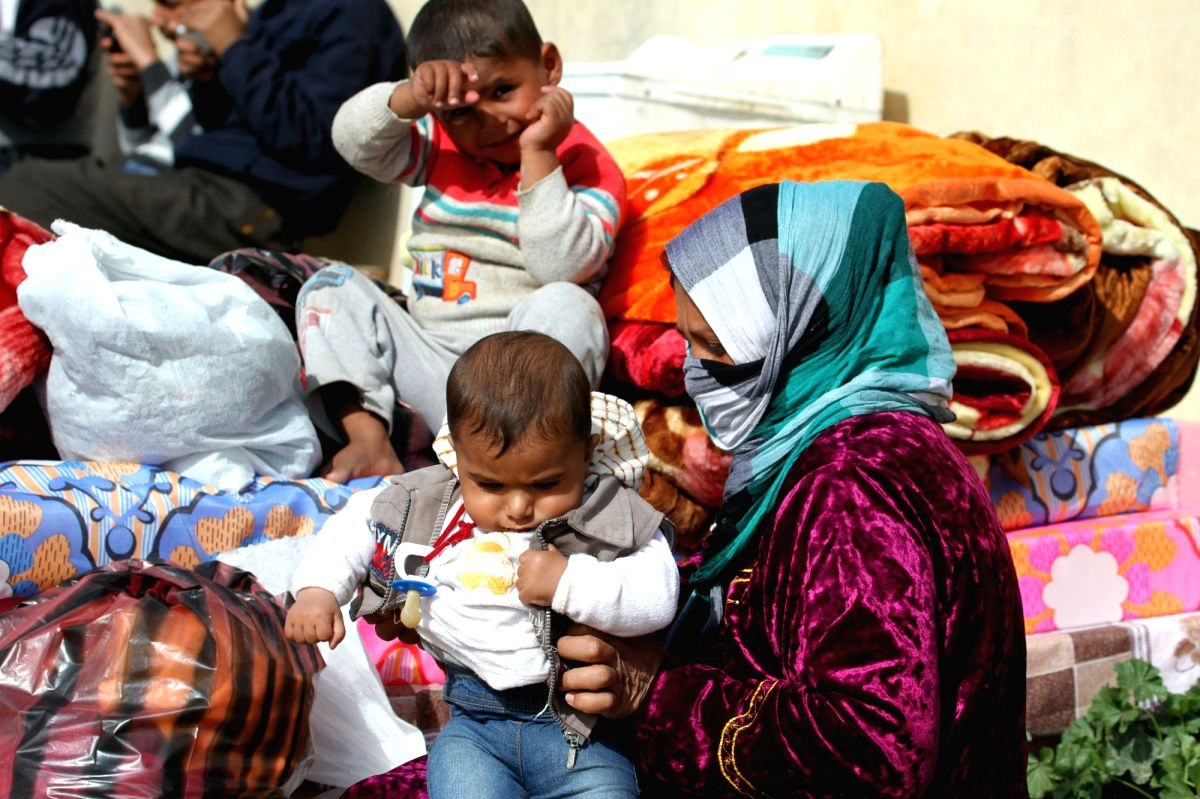 A refugee family are seen outside their makeshift home in Erbil, the capital city of Iraqi Kurdish region