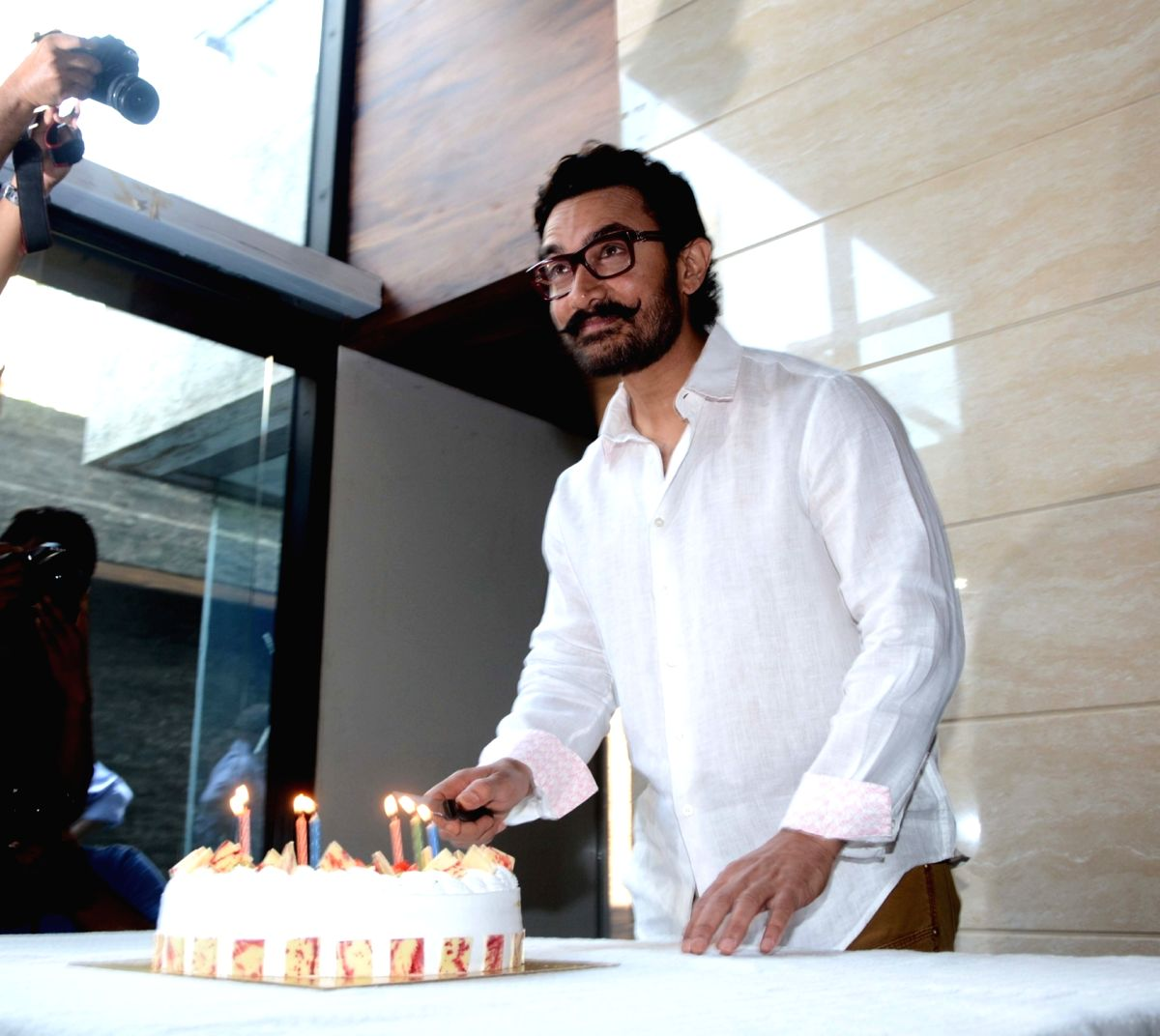 Actor Aamir Khan cuts a cake to celebrate his 52nd birthday in Mumbai on March 14, 2017.