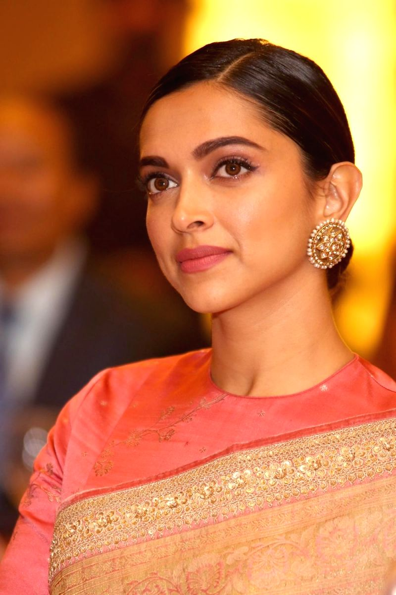 Deepika looks sophisticated in this lovely salmon colored saree, complete with a pair of traditional stud earrings