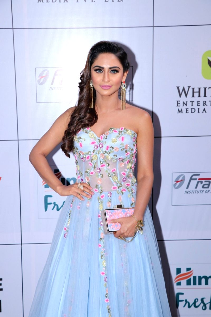 Krystle D'souza  looks breathtaking in this ice-blue strapless gown with sweetheart neck and floral detailing. Special points for the dangle earrings and curls.