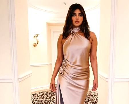 Actress Priyanka Chopra Jonas on Sunday shared her pre-Grammys' party look. Wearing a champagne  satin backless gown, Priyanka is definitely leaving her fans in awe of her fashion statement.