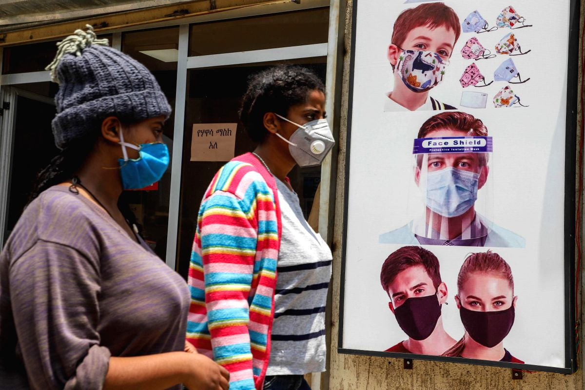 Addis Ababa, Aug. 22, 2020 (Xinhua) -- People wearing face masks walk past a poster promoting the use of face mask and face shield in Addis Ababa, capital of Ethiopia, Aug. 21, 2020. Ethiopia's confirmed COVID-19 cases reached 39,033 after 1,368 new