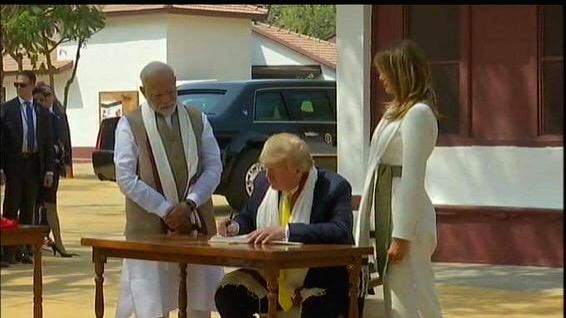 Ahmedabad: US President Donald Trump signs the Visitors Book of the Sabarmati Ashram as US First Lady Melania Trump and Prime Minister Narendra Modi look on, in Ahmedabad on Feb 24, 2020.