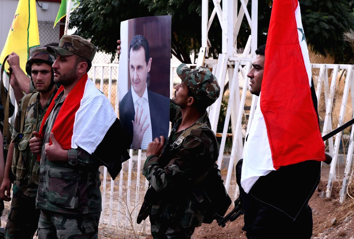 ALEPPO (SYRIA), Oct. 18, 2019 (Xinhua) -- A Syrian soldier holds a poster of Syrian President Bashar al-Assad in the town of Ayn al-Arab in northern Syria, Oct. 18, 2019. The Syrian army on Wednesday entered the symbolically important Kurdish-held to