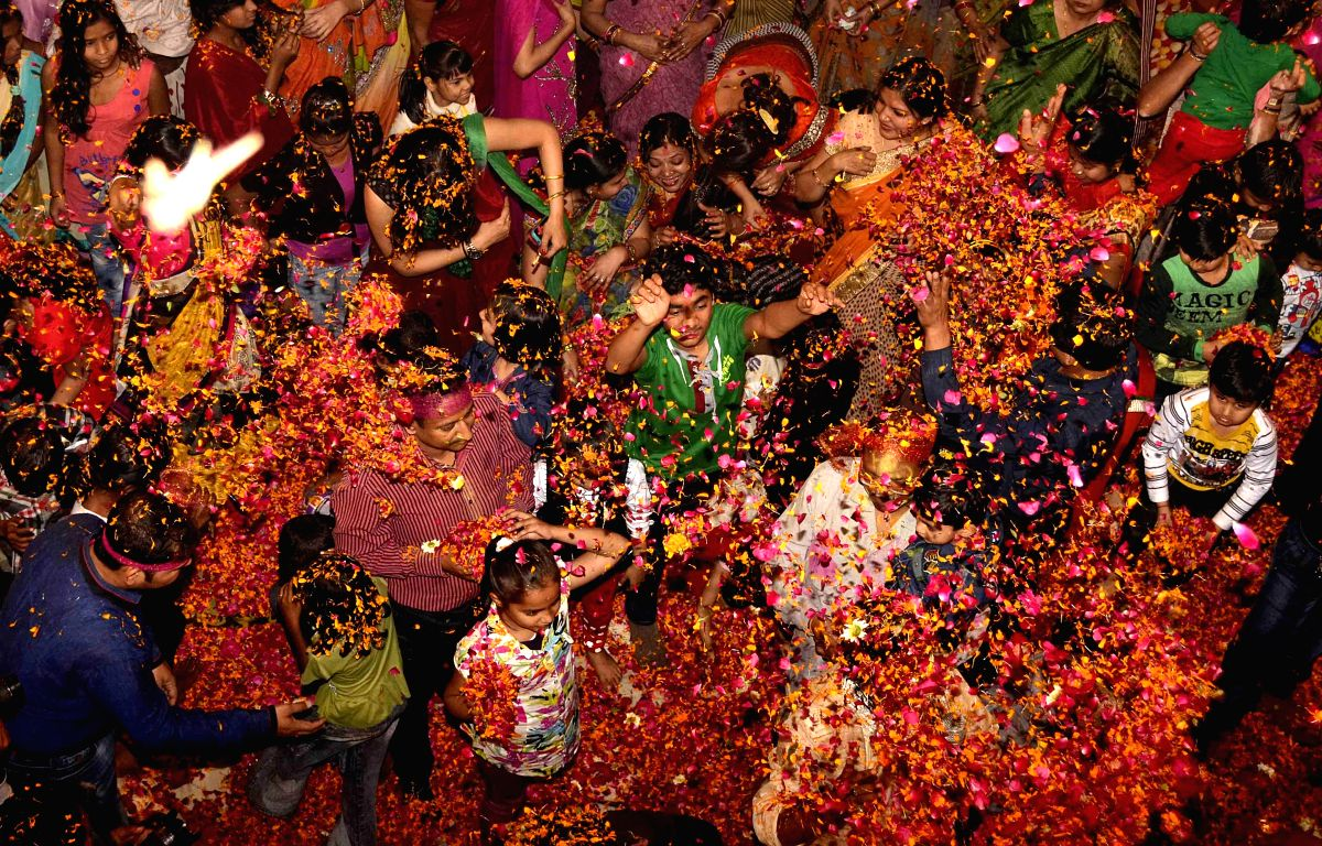 People play Holi with flower petals in Allahabad.