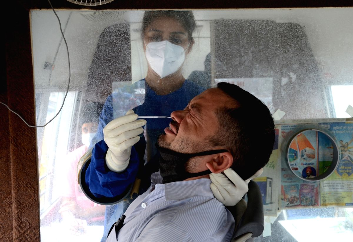Amritsar: A health worker takes a nasal swab sample from a person for COVID-19 tests inside a mobile van, amid a surge in coronavirus cases in Amritsar on Friday, 28 May, 2021.  (Photo:Pawan sharma/IANS)