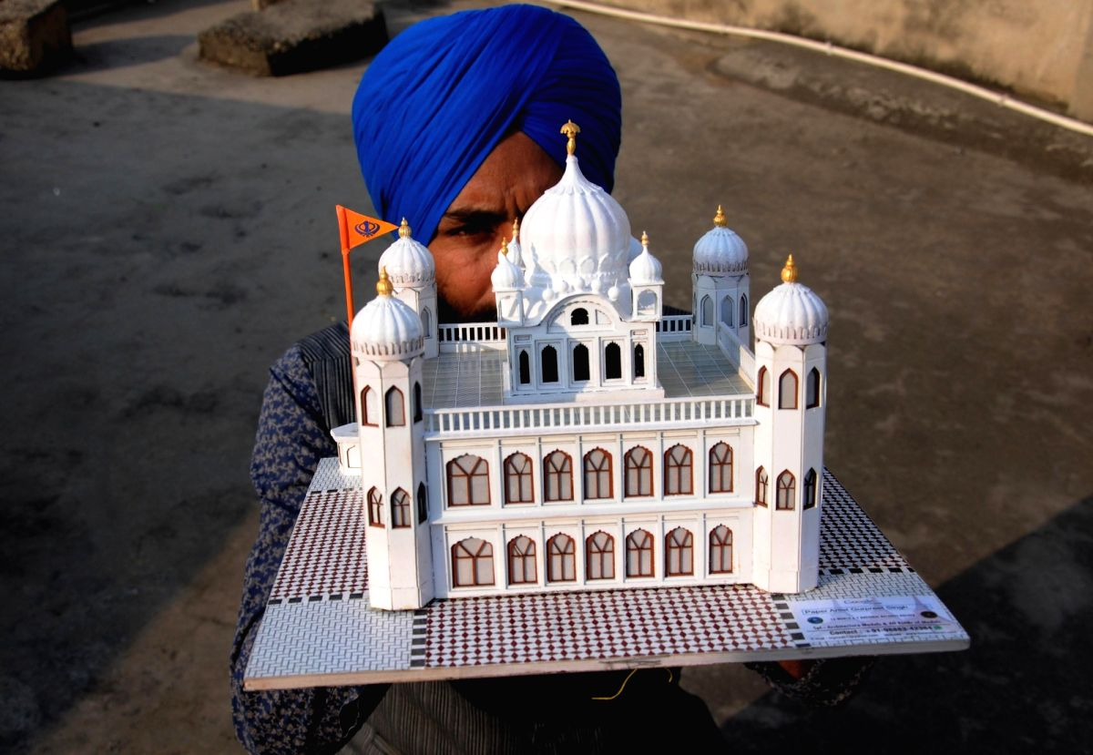 Amritsar: Paper artist Gurpreet Singh shows a model of Kartarpur Sahib, the final resting place of Guru Nank Dev, created by him, on the eve of the first Sikh Guru's birth anniversary, in Amritsar on Nov 22, 2018.