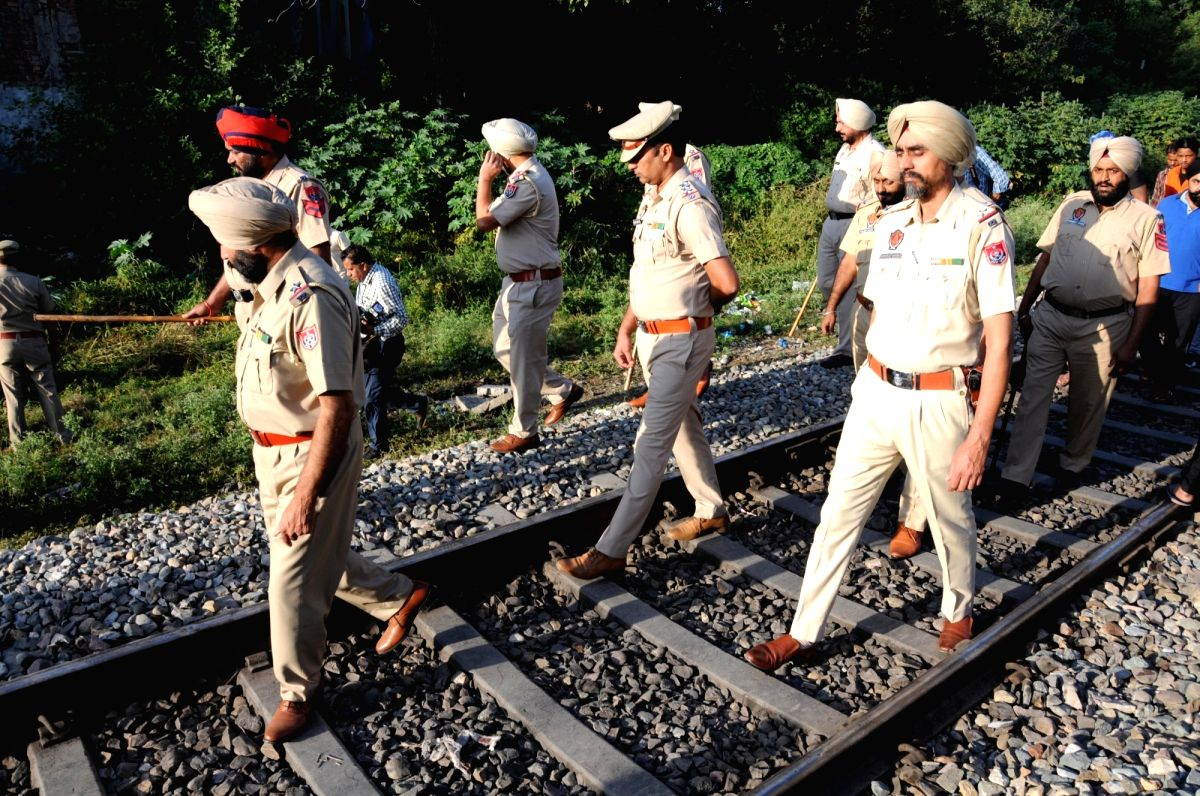 :Amritsar: Punjab police personnel during investigation at the site where a local train crushed at least 58 people and left 72 injured while watching the burning of a Ravana effigy from a railway ...
