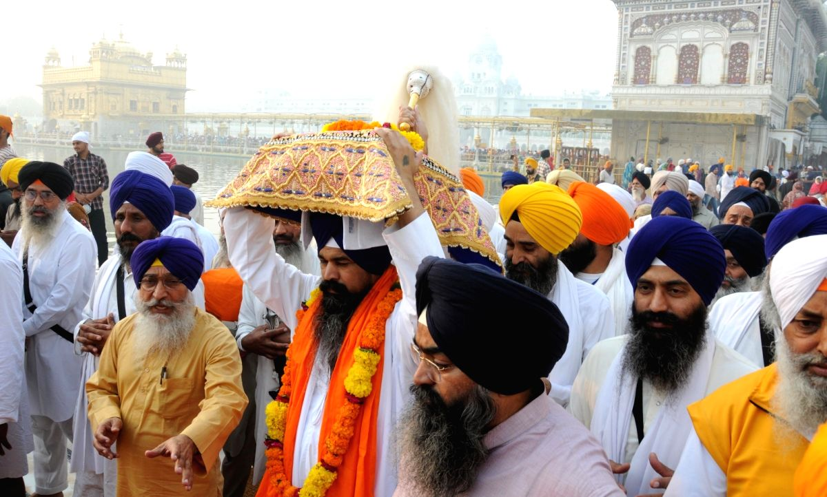 Amritsar: Sikh devotees carry Sri Guru Granth Sahib to Pakistan during a special religious procession organised to mark the 550th birth anniversary celebrations of Guru Nanak Dev in Amritsar on Oct 31, 2019.The religious procession arrived from Delhi