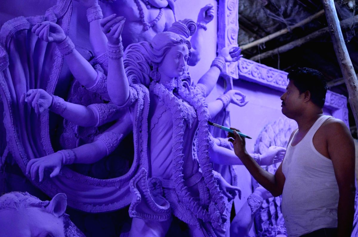 An artist adding last minute touches to the Durga idol ahead of Durga  Puja celebrations