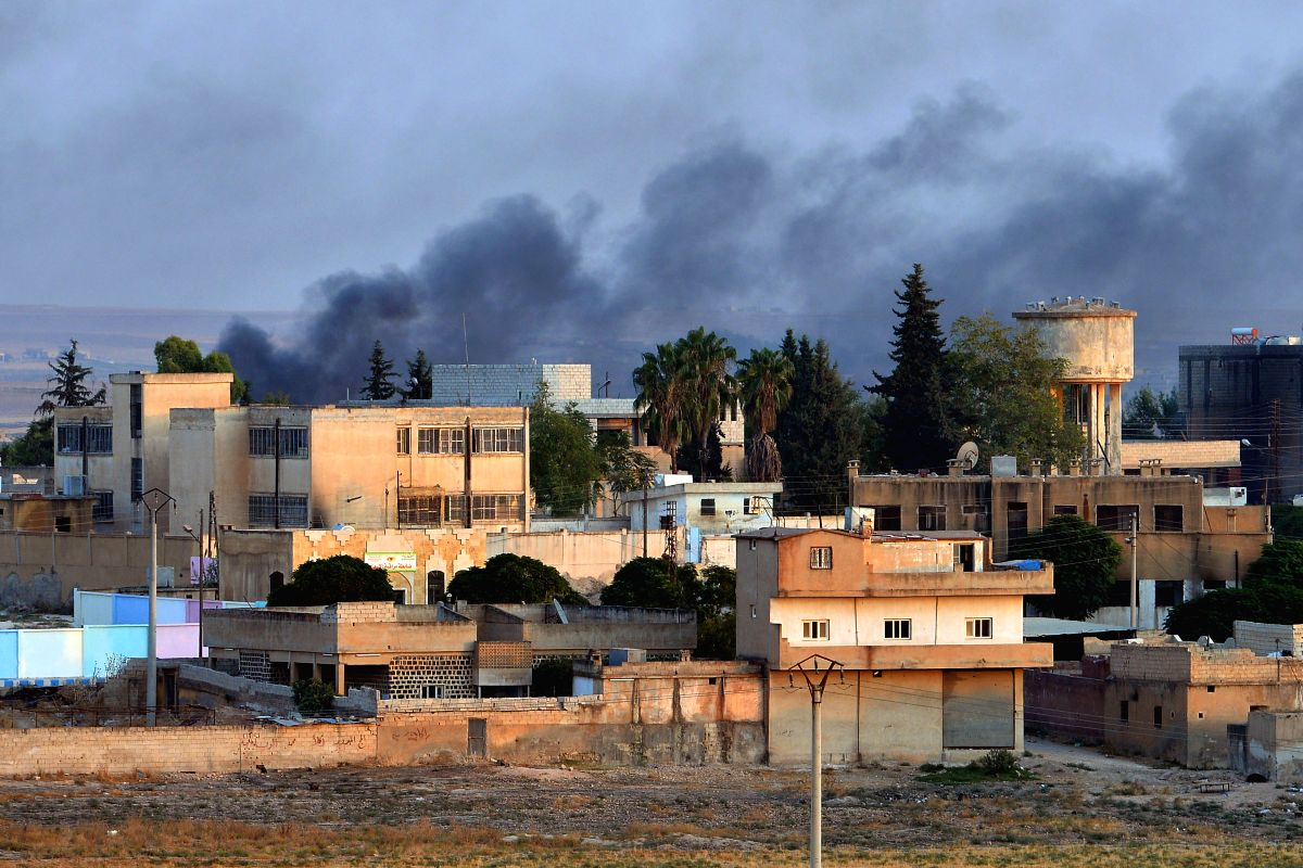 ANKARA, Oct. 15, 2019 (Xinhua) -- Photo taken from Turkish border town of Akcakale on Oct. 13, 2019 shows smoke rising from Tal Abyad in northern Syria during an attack. Turkish Armed Forces have taken control of Tal Abyad and Ras Al-Ayn towns in nor