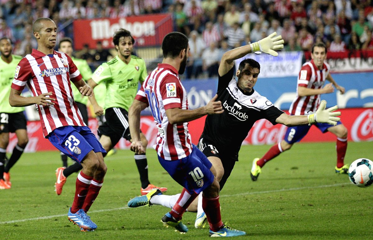 : Atletico de Madrid´s Turkish midfielder Arda Turan (C) pases the ball next to Brazilian Joao Miranda (L) and Osasuna´s goalkeeper Andres Fernandez (R) during their Spanish Liga Primera Division ...