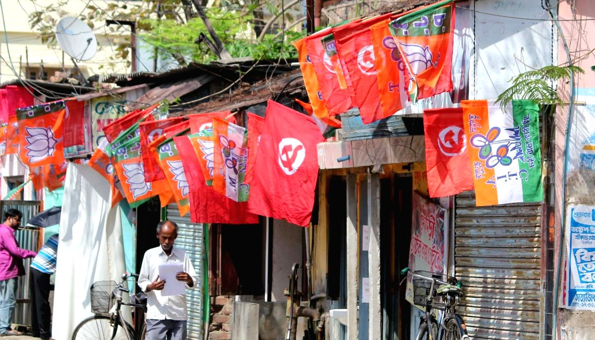 Balurghat: Flags of various political parties are on display at a roadside shop in Balurghat of West Bengal, on April 9, 2016.