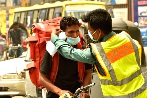 Bangladesh: A policeman gives a mask to a rickshaw puller on a street in Dhaka, Bangladesh. (Xinhua/IANS)