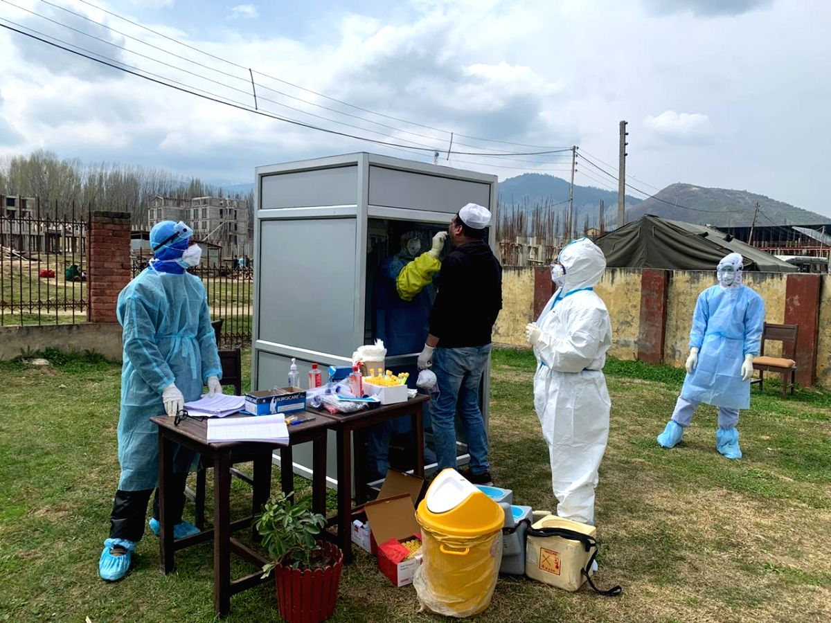 Baramulla: A medical worker collects sample from a person for COVID-19 tests at a 'Booth type sampling Centre' set up in Jammu and Kashmir's Baramulla amid cornavirus pandemic, on Apr 7, 2020. (Photo: ANS)