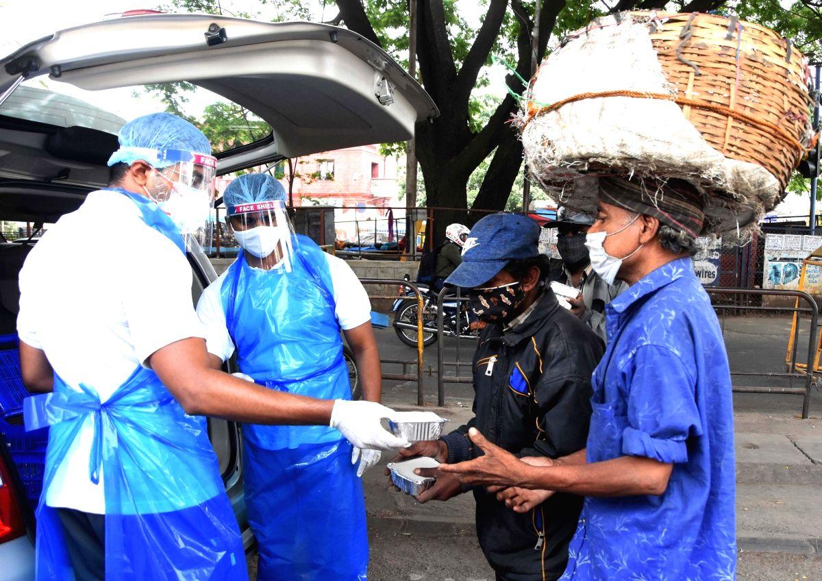 Bengaluru: Volunteers distributed free food for poor people at KR Market during the Coronavirus Pandemic, in Bengaluru on Saturday 1st May 2021.(Photo: Dhananjay Yadav/IANS)