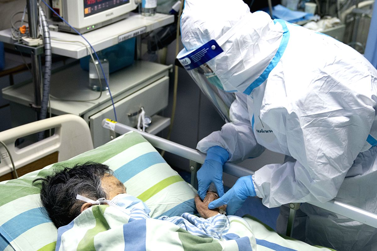 Chief nurse Ma Jing holds a patient's hand to comfort her in the ICU (intensive care unit) of Zhongnan Hospital of Wuhan University in Wuhan. (Xinhua/Xiong Qi/IANS)