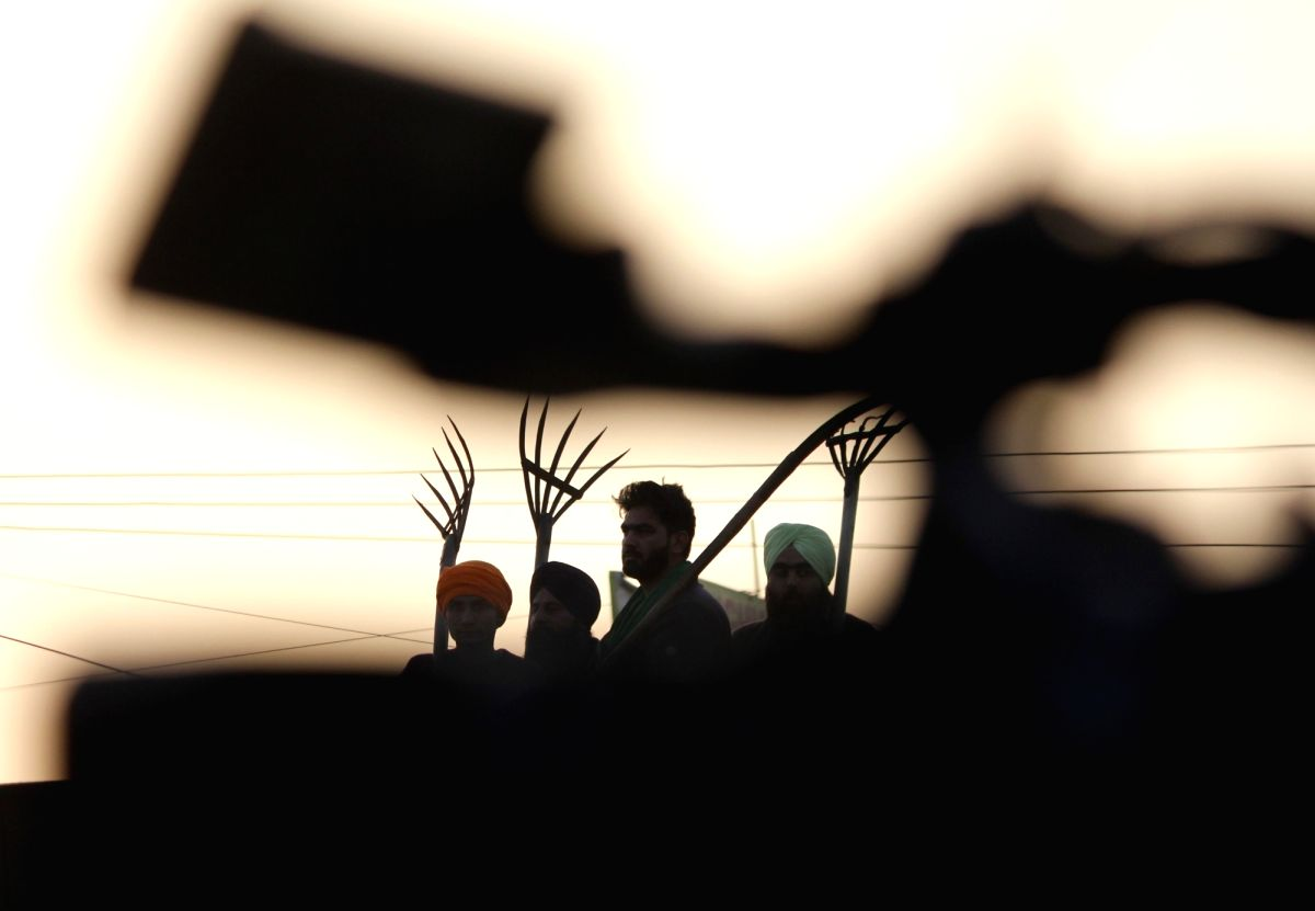 Farmers during sunset, on the 19th day of their ongoing protest against the Centre's new farm laws, at Delhi-Haryana's Singhu Border on Dec 14, 2020.