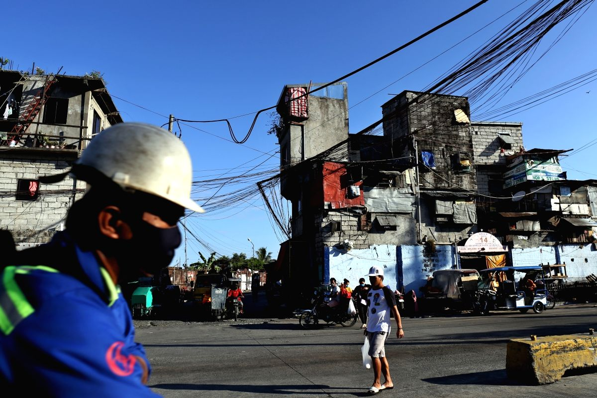 FILED - People walking in a street in a slum in Manila. Social distancing in these areas to prevent the spread of coronavirus is almost impossible. Photo: Alejandro Ernesto/dpa/IANS