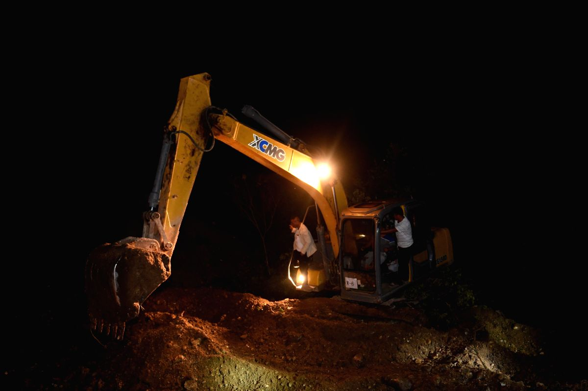 FUNING, Aug. 24, 2015 (Xinhua) -- Rescuers search for the missing at the site of landslide at a village in Funing County, southwest China's Yunnan Province, Aug. 23, 2015. Three people have been confirmed dead after their bodies were dug out from the