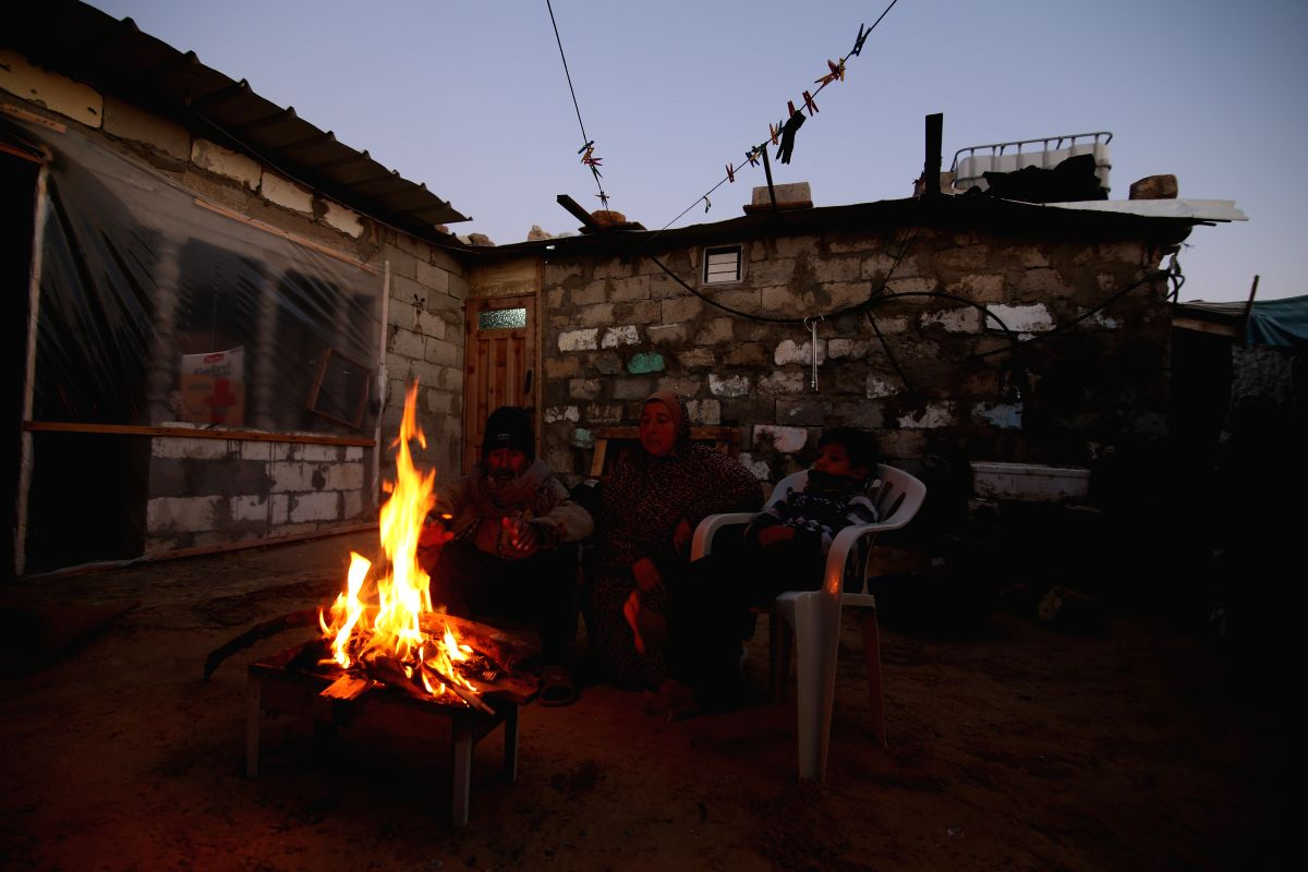 GAZA, Dec. 29, 2016 (Xinhua) -- A Palestinian family warm up in front of a fire during a power outage outside their house during rainy, cold weather in a slum on the outskirts of the southern Gaza Strip city of Khan Younis, on Dec. 28, 2016. Resident