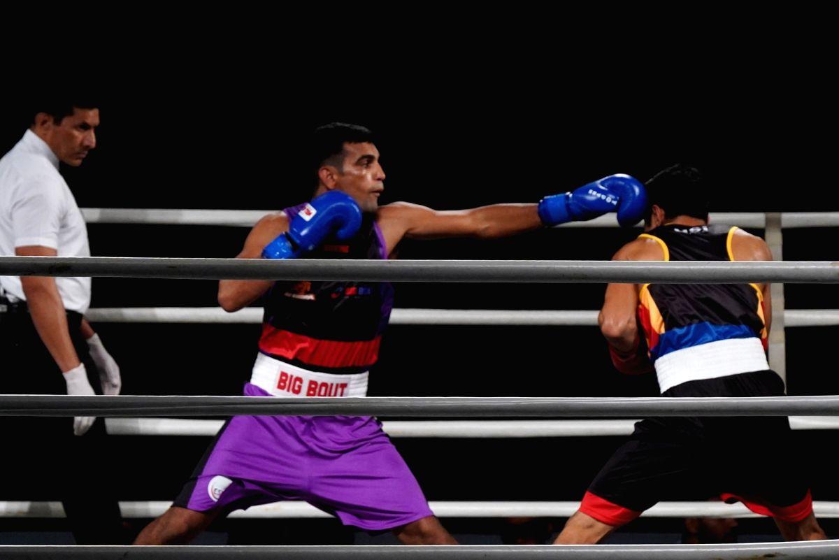 Greater Noida: NE Rhinos' Mandeep Jangra in action against Bengaluru Brawlers' Dinesh Dagar during Big Bout Indian Boxing League at the Gautam Buddha University in Greater Noida, Uttar Pradesh on Dec 3, 2019.