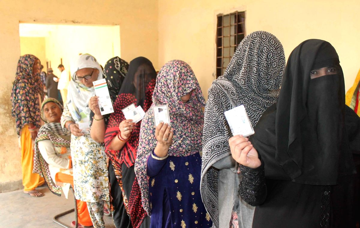 Gurugram: Women waiting in a queue to cast their votes for Haryana Assembly elections, show their Voter Id cards, at a polling station in Gurugram on Oct 21, 2019.