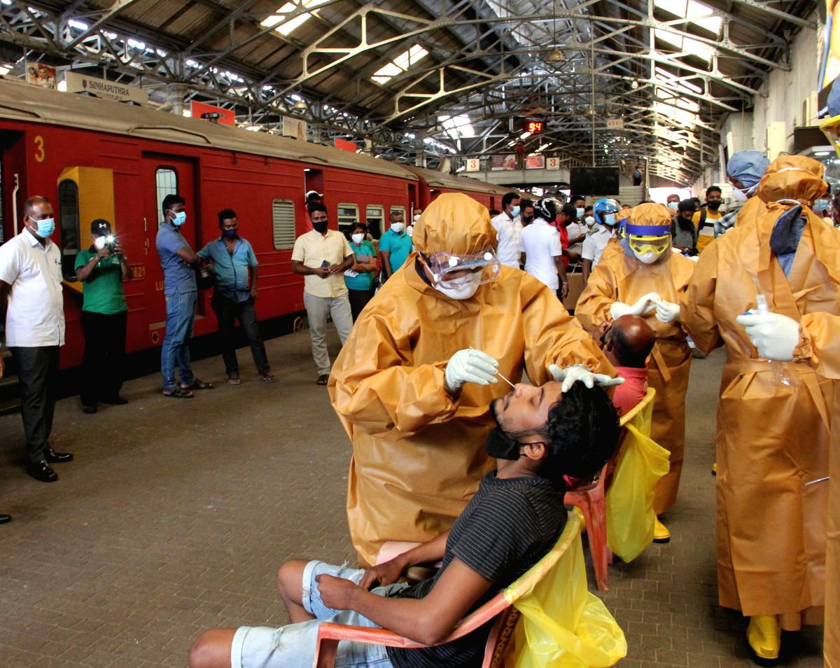Health workers conduct PCR tests on workers at the Fort Railway Station in Sri Lanka's capital Colombo. (Photo by Ajith Perera/Xinhua/IANS)