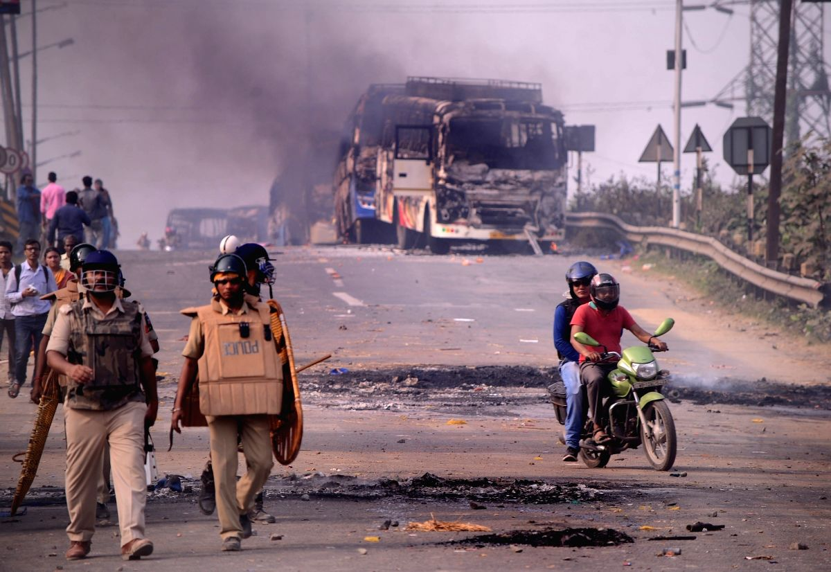 Howrah: Police personnel patrol a street after violence broke out as angry protesters burnt vehicles during a demonstration against the Citizenship Amendment Act (CAA) 2019, in West Bengal's Howrah on Dec 14, 2019. Violent protests against the new ci