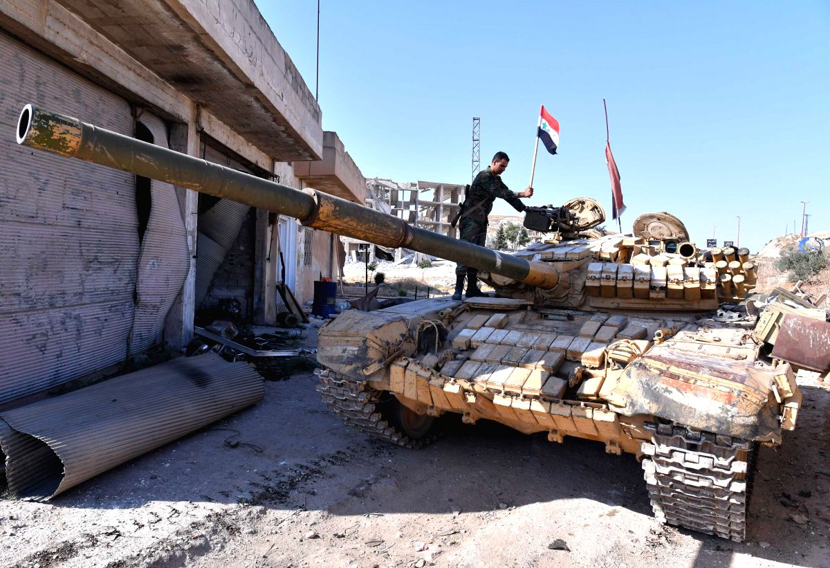IDLIB (SYRIA), Aug. 24, 2019 (Xinhua) -- A Syrian soldier puts a Syrian flag on the top of a tank in the town of Khan Shaykhun in the southern countryside of Idlib province, Syria, on Aug. 24, 2019. The Syrian army on Friday fully secured the entire