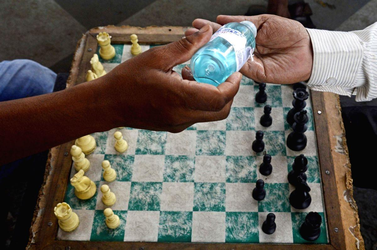 Kolkata: People sanitise their hands and play chess at boulevard of Gariahat in Kolkata amid COVID-19 pandemic, on June 13, 2020. (Photo: Kuntal Chakrabarty/IANS)