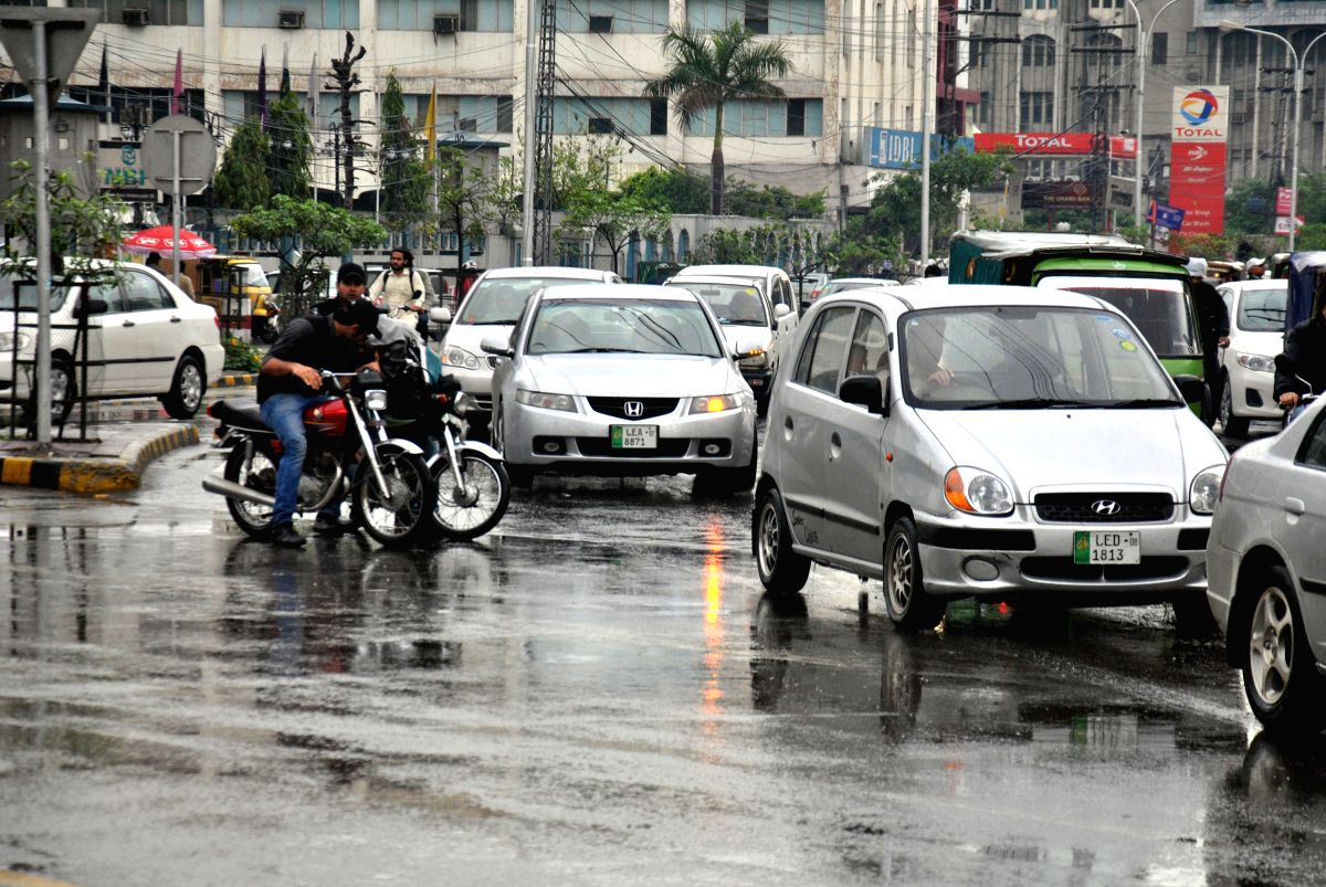 LAHORE, March 28, 2014 (Xinhua) -- Vehicles move on a road during a rainy day in eastern Pakistan's Lahore on March 28, 2014. Scattered rain and thunderstorms have been forecast to grip many parts of the country. (Xinhua/Sajjad/IANS)(bxq)